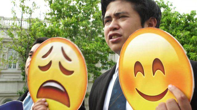 Filipino student holds up emojis
