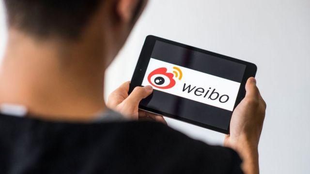 Человек с планшетом с логотипом Weibo