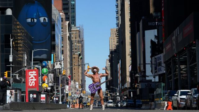 A minor New York celebrity who poses for tourist photos as the Naked Cowboy wears a mask in mostly deserted Times Square