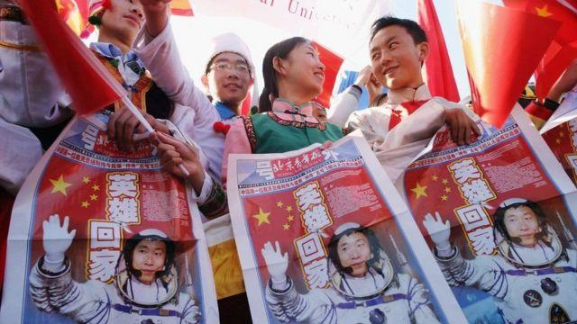 pessoas seguram jornais com primeiro astronauta chinês a viajar para o espaço