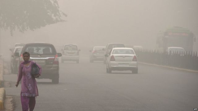 An Indian woman walks on a road during heavy smog conditions in New Delhi on November 7, 2017.