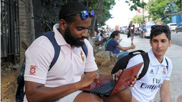 Homem usando laptop em Cuba