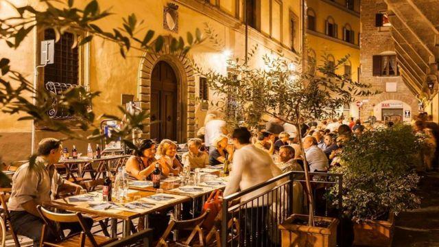 Comensales al aire libre en una ciudad italiana