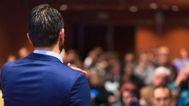 Una persona de espaldas, dando una charla a una audiencia