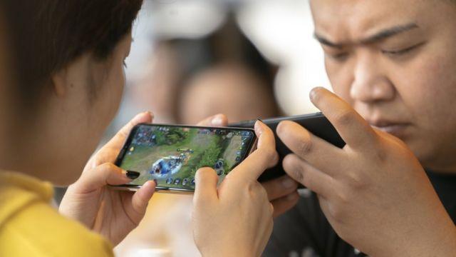 Dos personas una en frente de otra jugando en sus teléfonos.