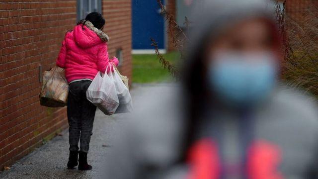 Em Baltimore, EUA, uma mulher anda pela rua carregando alimentos doados por voluntários