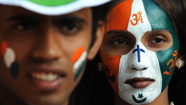 चेहरे पर चारों धर्म के प्रतीकों को पेंट किए हुए युवती
