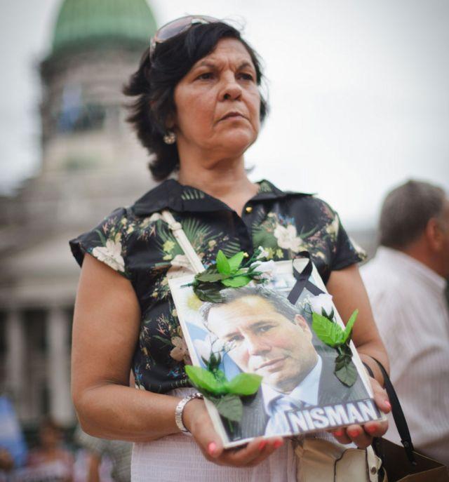 Una mujer sostiene un cartel con el rostro de Alberto Nisman durante una marcha