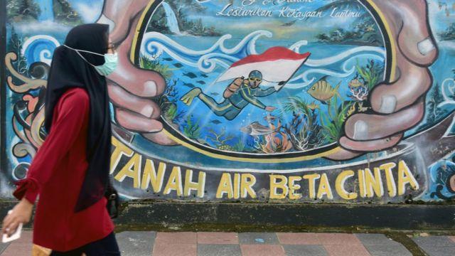 Warga mengenakan masker saat berjalan di dekat sebuah mural di Kota Ambon, Maluku, Rabu (7/7/2021).