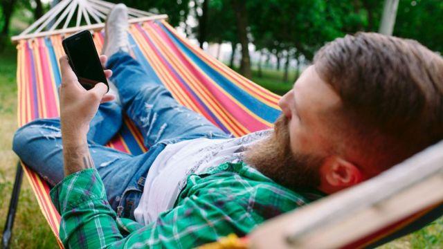 Homem deitado na rede olhando celular