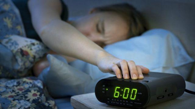 Una mujer cansada intenta apagar un despertador.