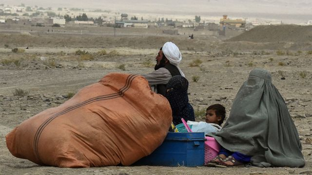 People forced to leave their homes wait for a border crossing to open