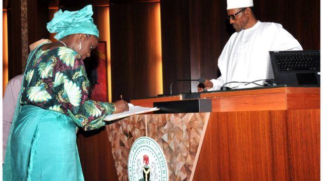 Kẹmi Adeọṣun n buwọlu iwe niwaju aarẹ Buhari