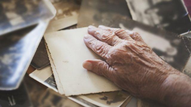 Mano de anciano sobre fotos antiguas