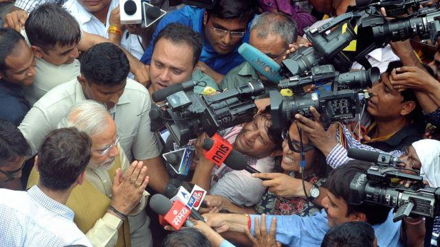 मीडिया के कैमरों से घिरे प्रधानमंत्री नरेंद्र मोदी