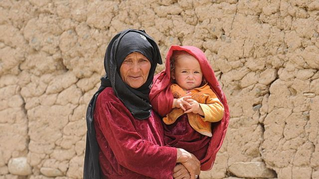 Idosa carrega bebê no Afeganistão