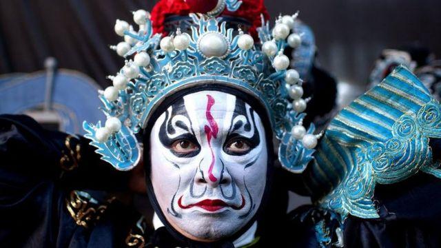 Homem com fantasia e maquiagem típicas da China