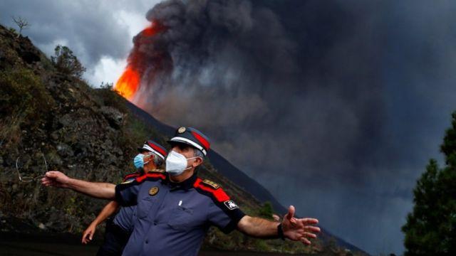 Policías con la erupción del volcán detrás.