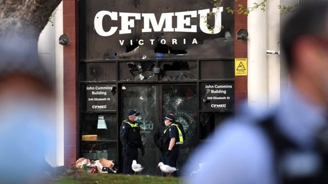 Police officers inspect a smashed façade at the Construction, Forestry, Maritime, Mining and Energy Union (CFMEU) headquarters in Melbourne, Victoria, Australia, 20 September 2021