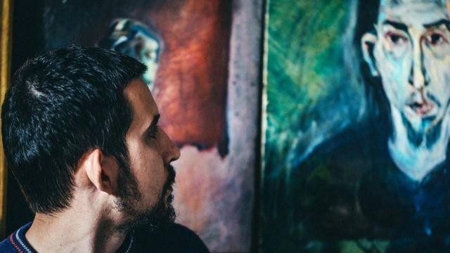 Hombre mirando un retrato.