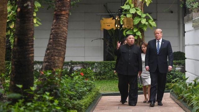 US President Donald Trump walks with North Korea's leader Kim Jong Un during a break in talks