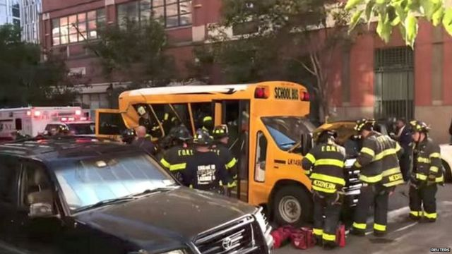 Authorities attend to a school bus damaged in the truck attack in New York City
