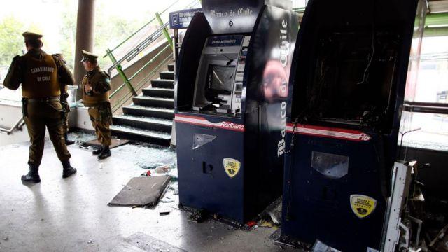 Na foto, dois caixas eletrônicos quebrados em uma estação de metrô