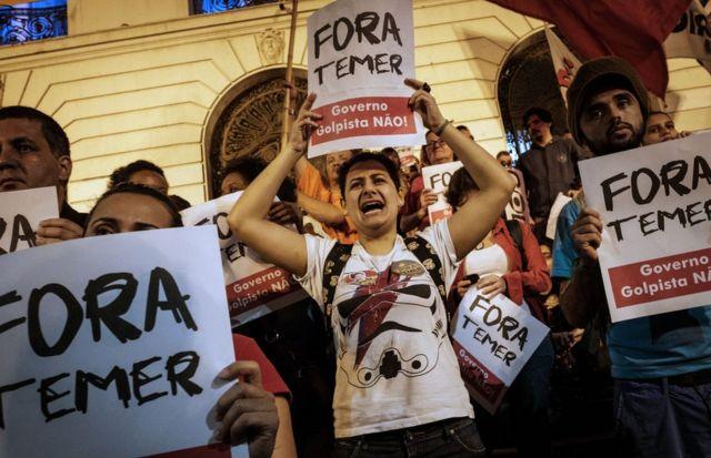 Ciudadanos sujetan carteles en protesta contra Temer.