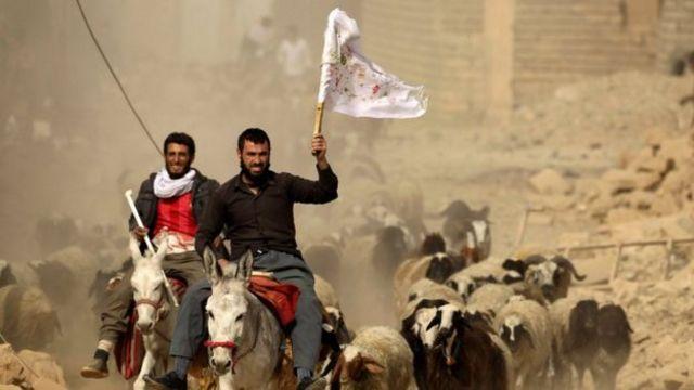 سكان بلوحون بالاعلام البيضاء في قرية بزوايا