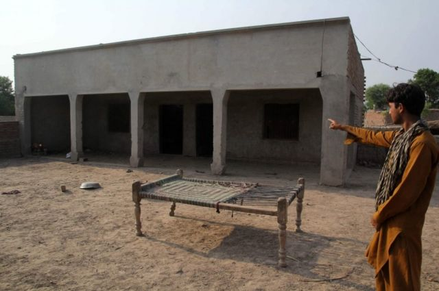 10代の少女がレイプされた家を指さす村の住人(パキスタン東部ムルタン郊外)