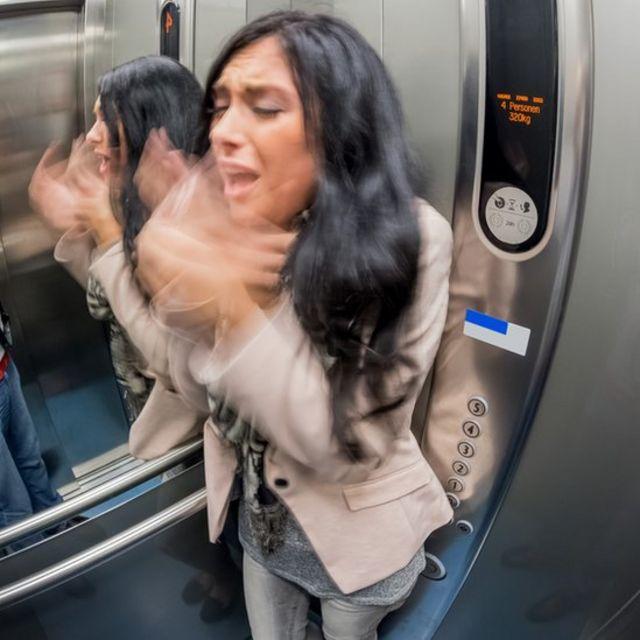 Mujer con ataque de pánico en un ascensor.