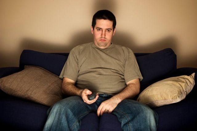 Homem no sofá assistindo à TV
