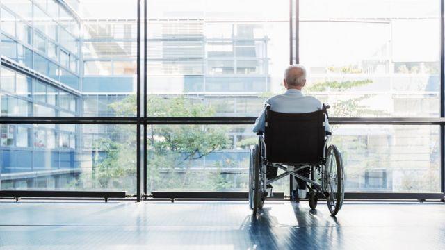 seorang lansia menggunakan kursi roda.