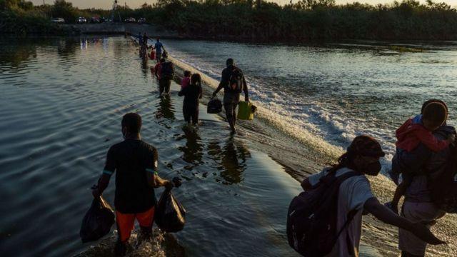Migrantes cruzando Río Grande.