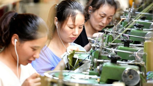 This photo taken on August 13, 2018 shows employees working on a production line of clothes for export at a factory in Xiayi county, in Shangqiu in China's central Henan province. -