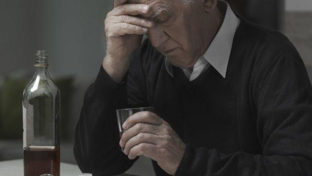 Un hombre deprimido bebiendo alcohol