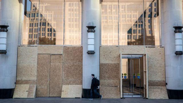 Una tienda en Nueva York con tablones de madera tapando sus vitrinas.