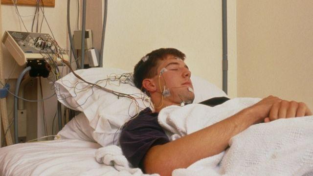 Voluntário dormindo, com cabos conectados à cabeça