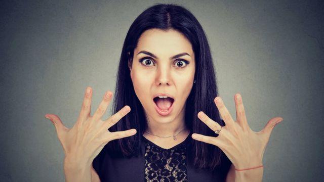 Mujer con cara de sorpresa mostrando las uñas.