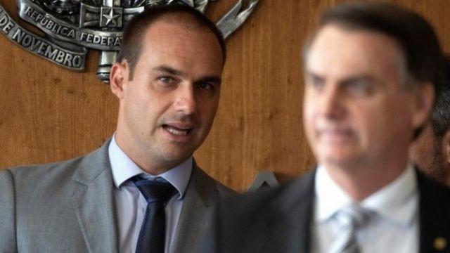 Eduardo Bolsonaro e Jair Bolsonaro, desfocado, está à frente do filho