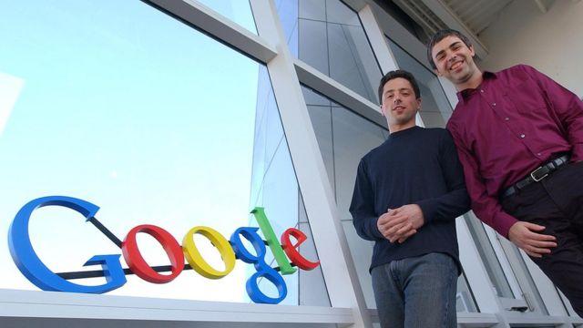 Co-fundadores de Google, Larry Page y Sergey Brin, junto al cartel de la empresa.