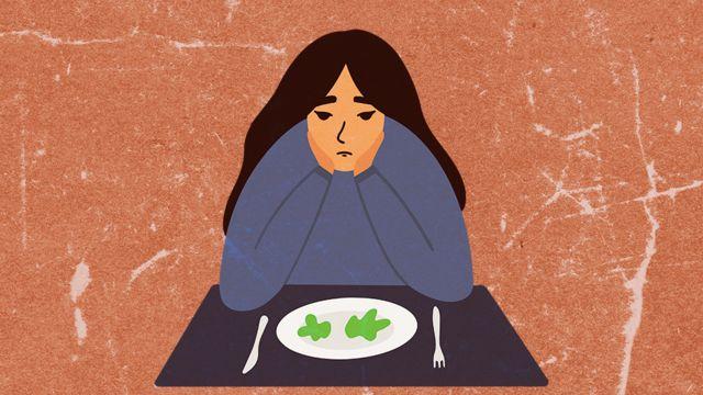 Mulher sentada à mesa com um prato quase vazio