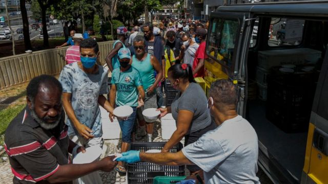 Pessoas em situação de rua recebem marmitas nas ruas de São Paulo. Março de 2021