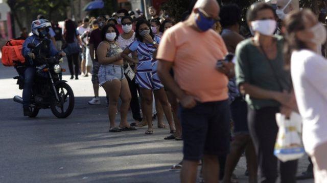 Dezenas de pessoas com máscaras enfileiradas em rua do Rio de Janeiro