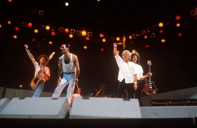 """Триумфальное выступление Queen на концерте Live Aid на стадионе """"Уэмбли"""". 13 июля 1985 г. Слева направо: Джон Дикон, Фредди Меркьюри, Роджер Тейлор, Брайан Мэй."""
