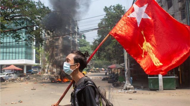 Manifestante com bandeira de partido deposto por militares