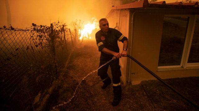 A firefighter tries to reach a hose to put out a house fire on the Greek island of Evia.