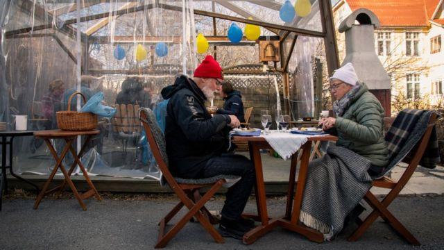 шведская пожилая пара обедает на террасе в ресторане, 2020г