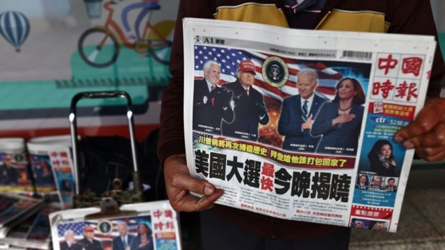 A man sells newspapers with front page articles about the US election along a street in Taipei