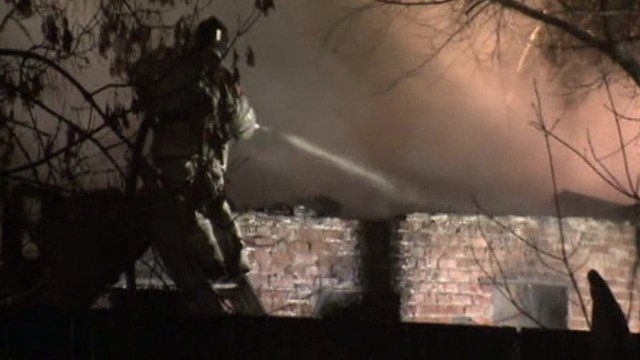 Firefighter spraying water at fire